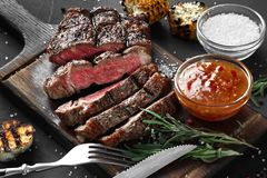 Sliced grilled medium rare beef steak served on wooden board Barbecue, bbq meat beef tenderloin. Top view, slate background royalty free stock photos