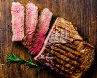 Sliced grilled medium rare beef steak served on wooden board Barbecue, bbq meat beef tenderloin. Top view, slate royalty free stock photo