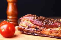 Sliced grilled pork ribs barbecue Striploin steak with chimichurri sauce and tomatoes on cutting board on dark royalty free stock photography