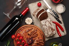 Sliced grilled pork steaks with bottle of wine, wine glass, corkscrew, knife, fork, black bread, cherry tomatoes, garlic, onion royalty free stock photography
