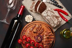 Sliced grilled pork steaks with bottle of wine, wine glass, corkscrew, knife, fork, black bread, cherry tomatoes, garlic, onion stock photography
