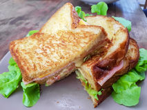 Sliced grilled sandwiches bread with bacon , ham, cheese and veg Stock Image