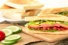 Sliced Grilled sandwiches bread with bacon , ham and cheese with Stock Image