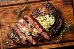 Sliced grilled steak Ribeye with herb butter. Sliced grilled Medium rare barbecue steak Ribeye with herb butter on cutting board close up Royalty Free Stock Photography