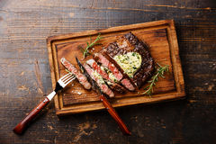 Sliced grilled steak Ribeye with herb butter. Sliced grilled Medium rare steak Ribeye with herb butter on cutting board on wooden background Royalty Free Stock Image