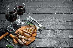 Sliced grilled steak with wine stock image