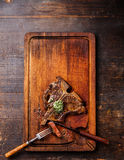Sliced grilled T-Bone Steak and herb butter. On cutting board on dark wooden background Royalty Free Stock Photo