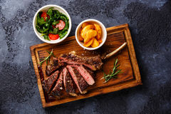 Sliced grilled Veal rib with potato wedges and salad Royalty Free Stock Photos
