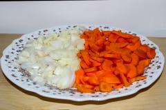Sliced högg av rå grönsaker - lökar och morötter Arkivfoto