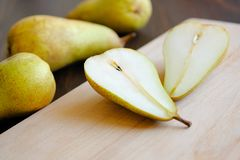 Sliced halves or slices of fresh sweet ripe yellow and green pears, next whole pears and cutting kitchen Board on a brown wooden stock image