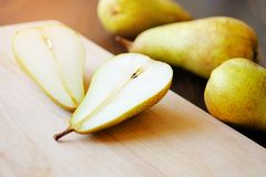 Sliced halves or slices of fresh sweet ripe yellow and green pears, next whole pears and cutting kitchen Board on a brown wooden royalty free stock photo