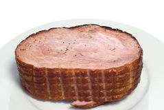 Sliced Ham. A cooked ham on a white plate, with spices on top, isolated against a white background Stock Images