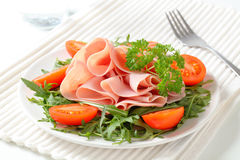 Sliced ham with arugula leaves and tomatoes Royalty Free Stock Photo