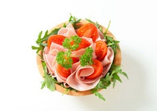 Sliced ham with arugula and tomatoes Royalty Free Stock Photo