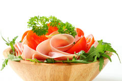 Sliced ham with arugula and tomatoes Stock Photography