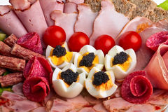 Sliced ham, bacon, salami dish. Sliced ham, bacon, salami rolls, boiled eggs with black caviar and more Royalty Free Stock Photos