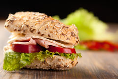 Sliced ham and cheese sandwich. Sliced ham sandwich with tomatos on a mixed seed bread Royalty Free Stock Photos