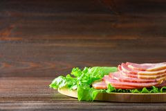 Sliced ham with fresh green lettuce leaves on a round cutting board. Meat products on a brown wooden table. Royalty Free Stock Images