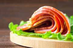 Sliced ham with fresh green lettuce leaves on a round cutting board. Meat products on a brown wooden table. Sliced ham with fresh green lettuce leaves on a Royalty Free Stock Photos