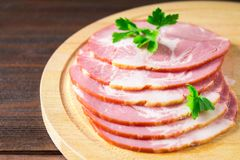 Sliced ham with fresh green lettuce leaves on a round cutting board. Meat products on a brown wooden table. Stock Photo