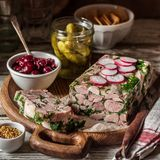 Ham Hock Terrine. Sliced Ham Hock Jelly Terrine with Pickles and Cranberry Sauce, square royalty free stock image