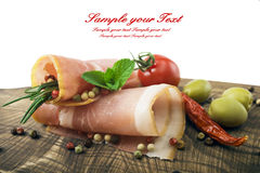 Sliced ham with rosemary, tomatoes and olives on a wooden table Royalty Free Stock Photos