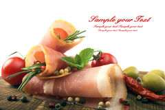 Sliced ham with rosemary, tomatoes and olives on a wooden table Royalty Free Stock Photography