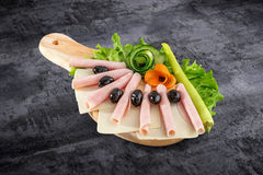 Sliced ham salami decorated on wooden board with olives, tomato and lettuce and clipping path Stock Photography