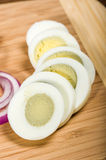 Sliced hard boiled egg on cutting board Royalty Free Stock Image