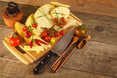 Sliced hard cheese on the kitchen board. Production of cheeses on the farm. Spicy cheese, tomatoes, garlic, chilli, pepper. Royalty Free Stock Images