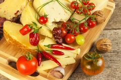 Sliced hard cheese on the kitchen board. Production of cheeses on the farm. Spicy cheese, tomatoes, garlic, chilli, pepper. Stock Photo