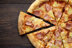 Sliced hawaiian pizza with ham and pineapple on dark wooden table. Top view, copy space, closeup stock photography