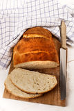 Sliced home baked bread loaf on a wooden board with knife Royalty Free Stock Photography