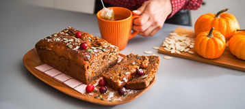 Sliced home-made loaf of pumpkin bread, womans hands and tea Royalty Free Stock Photography