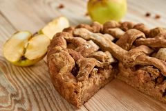 Sliced homemade american apple pie with fresh apples on brown wooden table. Homemade classical fruit tart with raisins. Close up view Stock Photo