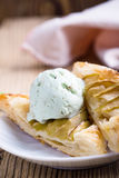 Sliced homemade apple tart with ice cream. Sliced homemade apple tart on rustic wooden board and served with ice cream on white plate Stock Photo