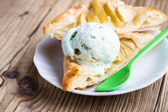 Sliced homemade apple tart with ice cream. Sliced homemade apple tart on rustic wooden board and served with ice cream on white plate Royalty Free Stock Photo