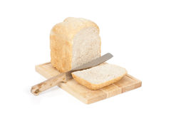 Sliced Homemade Bread Front Angeled View. An angled studio view of a loaf of homemade bread and a slice on a wooden breadboard with a bread knife Royalty Free Stock Image