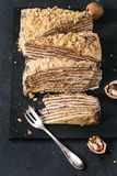 Sliced Homemade Honey Cake. With chocolate cream and walnuts, served with dessert fork and chopped nuts on black slate board. Top view Stock Photography