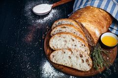 Sliced homemade italian ciabatta bread with olive oil on dark background. Ciabatta, herbs, olive oil, flour. Close up view, copy s royalty free stock photos