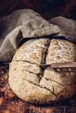Sliced rye bread with knife. Sliced homemade rye bread on cutting board with knife royalty free stock photography