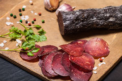 Sliced horse sausage, herbs and spices on cutting board. Selecti Royalty Free Stock Photo