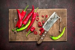 Sliced hot pepper on an old board. On a rustic background Stock Image
