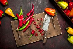 Sliced hot pepper on an old board. On a rustic background Stock Images