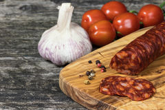 Sliced hot sausage Chorizo and vegetable on the wooden desk Stock Images