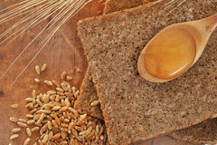 Sliced integral bread and honey spoon Royalty Free Stock Image