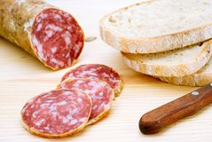 Sliced Italian Salami. A sliced italian salami on wood, shot with small DOF and with a knife and some bread Royalty Free Stock Photography