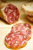 Sliced Italian Salami. A sliced italian salami on wood, shot with small DOF and with some bread Royalty Free Stock Photo