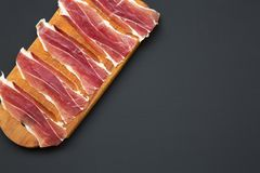 Sliced jamon Serrano or Iberico on cutting wooden board. Traditional spanish hamon on dark wooden background, top view. Copy space Royalty Free Stock Images