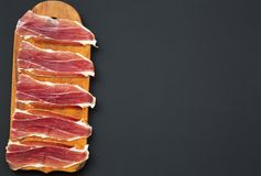 Sliced jamon Serrano or Iberico on cutting wooden board. Traditional spanish hamon on dark wooden background, top view. Copy space Stock Images